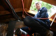 HVAC technician in attic crawlspace