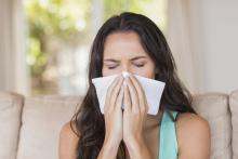 woman sneezing with indoor allergies