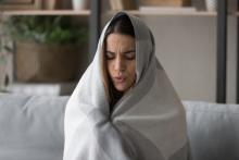 woman wrapped in blanket at home