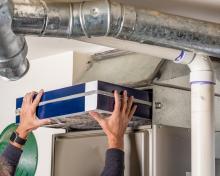 furnace repair man replacing a filter