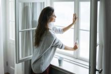 woman inside closing a window