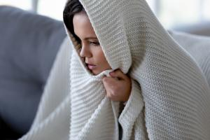 girl wrapped in blanket at home