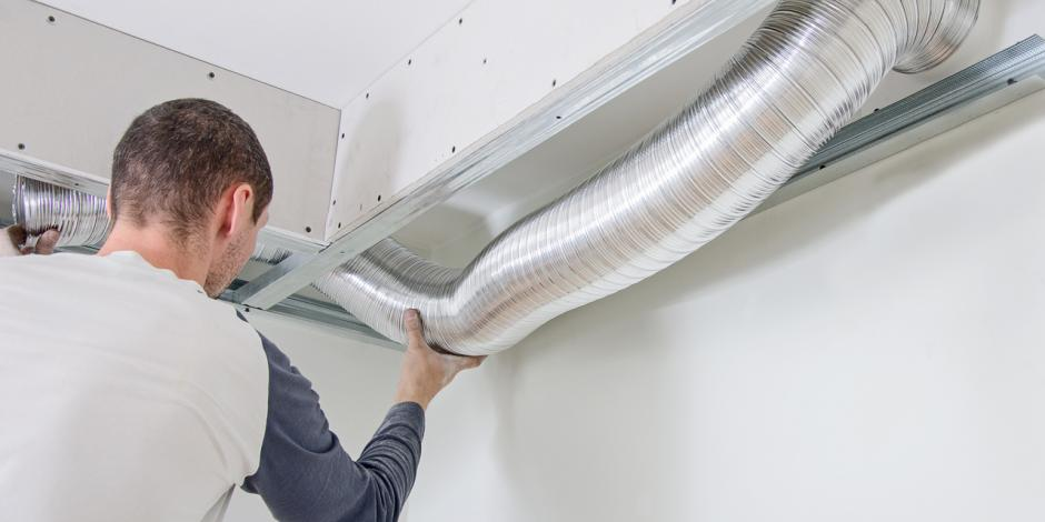 Greiner Heating & Air Conditioning, Man checking out ductwork indoors, CA