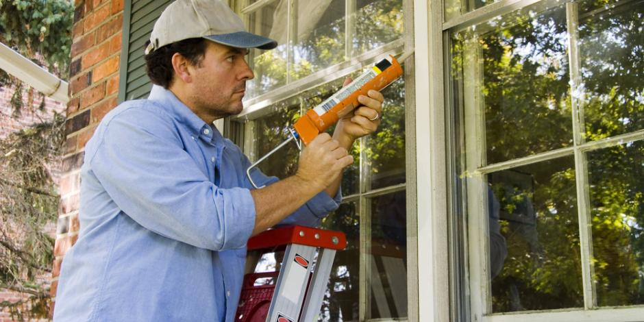 man sealing the outside windows of a house