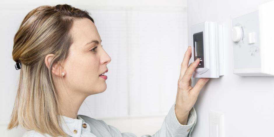 woman changing thermostat