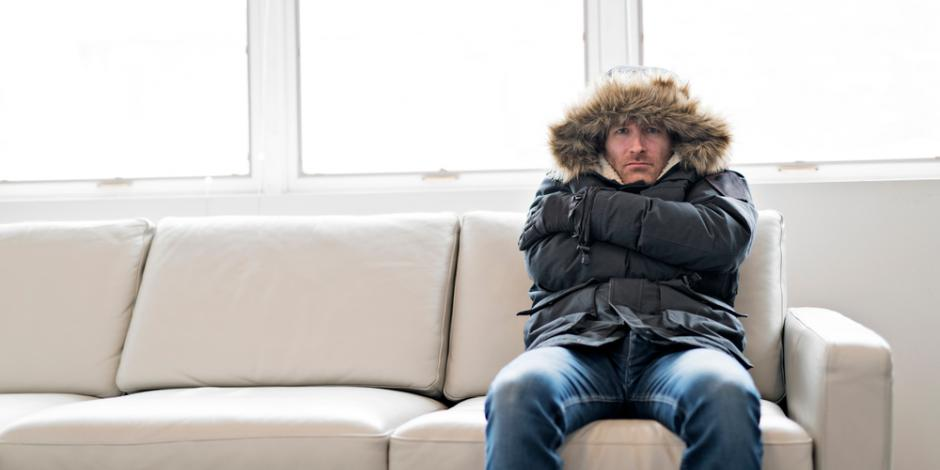 man in winter coat shivering inside cold home